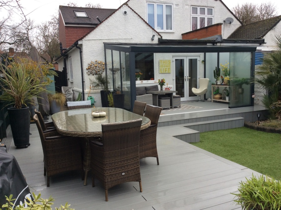 Garden with grey decking and sunroom